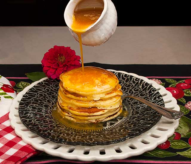 Sour cream pancakes dripping with orange sauce
